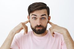 Bearded caucasian man close ears as standing in loud crowded place, holding index fingers in earholes pouting and. Raising eyebrows, reacting sound or noise stock photo