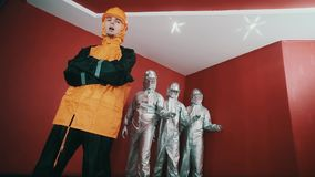 Man in hazard suit and hard hat rapping, trio in robot costumes snap fingers. Bearded caucasian man in hazard suit and orange hard hat rapping, trio in silver stock video