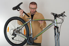 Bearded caucasian man putting a saddle on the mtb bicycle Stock Images