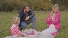 Bearded caucasian man shouting at his elder daughter on the autumn meadow. Blonde teenager defending herself and blaming. Younger sister dressed in dotted pink stock video footage