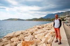 Bearded caucasian man, traveler walking along the marina royalty free stock photo