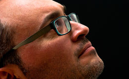 Bearded caucasian man wearing glasses looking up on black. Horizontal closeup of bearded caucasian man wearing glasses looking up on black Stock Images