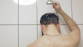 Bearded caucasian middle-aged man washes in the shower stock video footage
