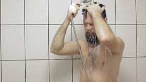 Bearded Caucasian middle-aged man washes in the shower stock footage