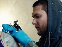 Bearded Caucasian tattooist stock image