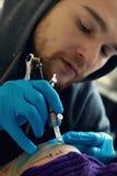 Bearded Caucasian tattooist Royalty Free Stock Image