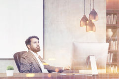 Bearded CEO in his office with bookshelves, toned. Portrait of bearded CEO sitting in his office and contemplating. Large white poster is behind him. 3d Stock Images