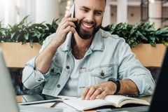Bearded cheerful man is sitting at table in front of laptops, talking on phone. Freelancer has telephone conversations. Young bearded cheerful man is sitting at stock images