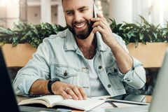 Bearded cheerful man is sitting at table in front of laptops, talking on phone. Freelancer has telephone conversations. Young bearded cheerful man is sitting at royalty free stock photos