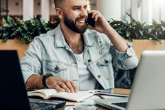 Bearded cheerful man is sitting at table in front of laptops, talking on phone. Freelancer has telephone conversations. Young bearded cheerful man is sitting at royalty free stock image