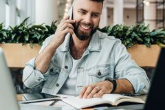 Bearded cheerful man is sitting at table in front of laptops, talking on phone. Freelancer has telephone conversations. Young bearded cheerful man is sitting at royalty free stock images