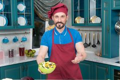Man holds plate with salad in hands on kitchen. Aged Chef in apron and hat made salad. Professional Cook at kitchen stock images