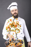 Bearded chef flipping vegetables in a frying pan Stock Photography