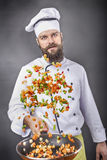 Bearded chef flipping vegetables in a frying pan Stock Photos