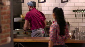 The bearded chef gives an order of a young waitress. stock footage