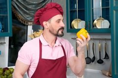 Bearded Chef in rose t-shirt sniffing yellow paprika on kitchen. Bearded Chef in red apron and red cap sniffing yellow paprika on kitchen. Yellow paprika in hand Stock Photo