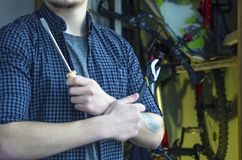 Bearded Classy Young Man with a Tattoo in a T-Shirt and Plaid Shirt Prepares To Maintenance Bicycle. Arms Crossed Holding Tools. stock photography