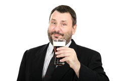 Bearded clerk holds a ale glass. Bearded clerk in black suit holds a ale glass on a white background Stock Photos