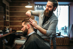 Bearded coiffeur cutting hairstyle by scissors. Bearded barber cutting male client hairstyle by scissors. Man in black salon cape at the barbershop royalty free stock photo
