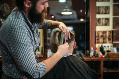 Bearded coiffeur cutting hairstyle by scissors. Client men in black salon cape sitting against a mirror at the barbershop royalty free stock image