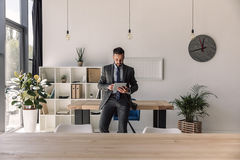 Bearded concentrated businessman using digital tablet in modern office. Young bearded concentrated businessman using digital tablet in modern office Royalty Free Stock Photos