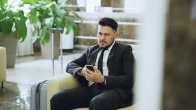 Bearded concentrated businessman using smartphone sit on armchair inside luxury hotel after arrivel to business meeting. Bearded concentrated businessman using stock video footage