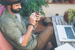 Bearded confident hipster wearing green shirt and brown hat texting message via smartphone on terrace outside. Positive. Man relaxing at summer day stock photography