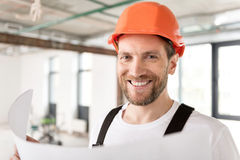 Bearded constructor demonstrating cheerfulness in room Stock Photography
