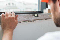 Bearded constructor making necessary renovation. Builder is using building level on window sit. He checking evenness of surface. Close up Royalty Free Stock Photos