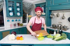 Bearded cook cutting yellow paprika. Smiling guy in cap makes salad with paprika. Bearded cook in apron and cap cutting yellow paprika. Smiling guy in cap makes Royalty Free Stock Image
