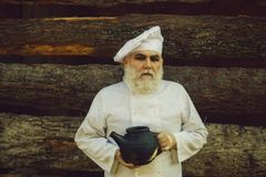Bearded cook with iron tea kettle stock image