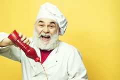 Bearded cook with ketchup bottle royalty free stock photos