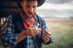 Bearded cowboy lights a cigar, wild west culture stock photo