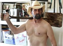 A Bearded Cowboy Puttering in His Tool Shed Royalty Free Stock Image