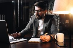 Bearded coworker sits by the wooden table with lamp and using contemporary notebook. Businessman hold pen and analysing trends. Young man working in loft stock image