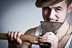 Bearded crazy woodcutter biting an ax Stock Image