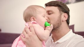 Bearded daddy kissing baby infant. Father kissing baby. Happy man with baby. Bearded daddy kissing baby infant. Close up of father holding child with toy. Father stock video footage
