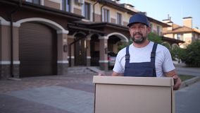 Employee of delivery service carrying box outdoors. Bearded delivery man in cap and overalls walking along street near townhouses holding cardboard box to stock footage