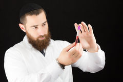 Bearded doctor holding test tube. Stock Photo