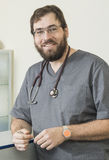 Bearded doctor wearing glasses and a gray robe Royalty Free Stock Images