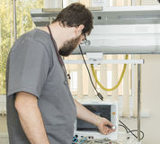 Bearded doctor wearing glasses and a gray robe works with hospital equipment Royalty Free Stock Image