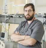 Bearded doctor wearing glasses and a gray robe works with hospital equipment Stock Images