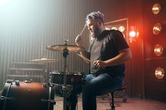 Bearded drummer with colorful hair, rock performer. On the stage with lights, vintage style. Musical concert in night club Royalty Free Stock Image