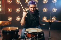 Bearded drummer with colorful hair, rock performer. On the stage with lights, vintage style. Musical concert in night club Royalty Free Stock Images