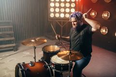 Bearded drummer with colorful hair, rock performer. On the stage with lights, vintage style. Musical concert in night club Royalty Free Stock Photography