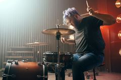 Bearded drummer with colorful hair on the stage. With lights, vintage style. Musical performer, live music performing stock image