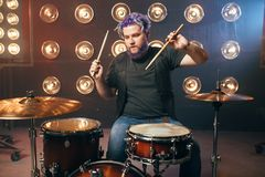 Bearded drummer with colorful hair on the stage. With lights, vintage style. Musical performer, live music performing stock photos