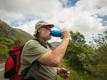 Bearded elderly man with a backpack in a landscape of Scotland. Active man with a red rucksack and drinking water in the mountains of Scotland, in the summer Stock Photo