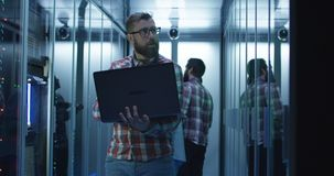Bearded IT engineer using laptop in server room. Adult bearded men using laptop while working in server room standing among racks with colleagues on background stock photography