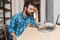 Bearded engineer waiting for program download. Free space. Programmer sitting at workplace with cup of coffee and looking at laptop screen, testing new Royalty Free Stock Photos